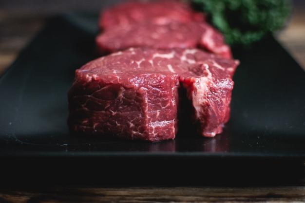10 alimentos surpreendentemente saudáveis bifes de carne crua em um prato preto